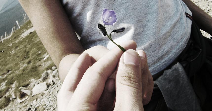 facet wręcza kwiatek dziewczynie